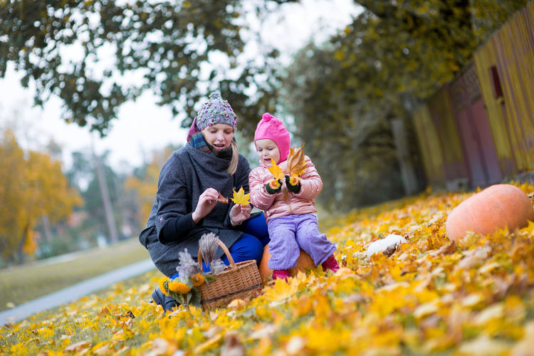 Mother and child in autumn leaves