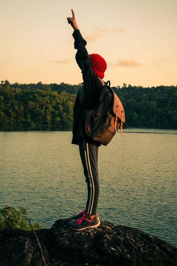 Full length of girl standing at lake against sky