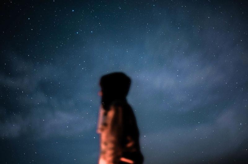 Defocused image of man standing against sky at night