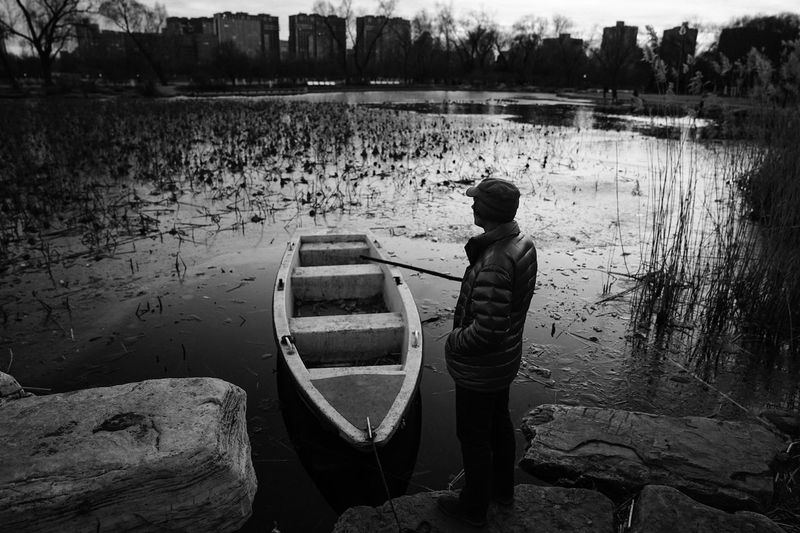 Rear view of man standing on boat moored in lake