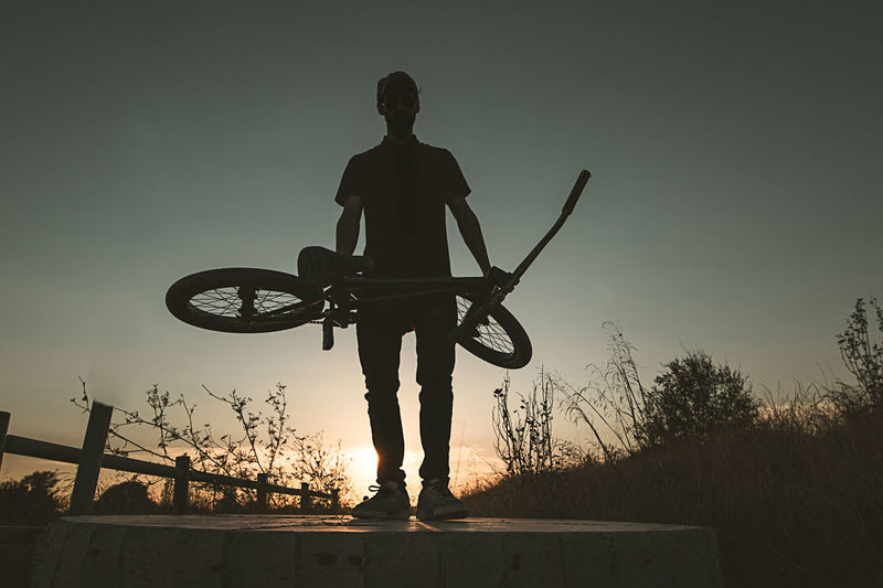 Rear view of silhouette man standing by bicycle against sky