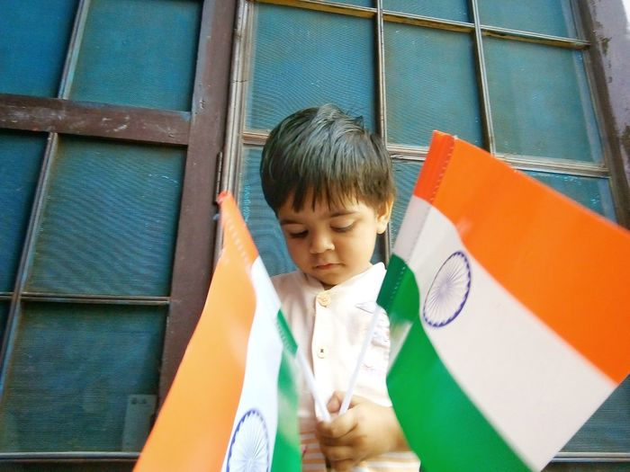 Boy holding flags outside house
