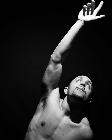 Shirtless Man Gesturing Against Black Background