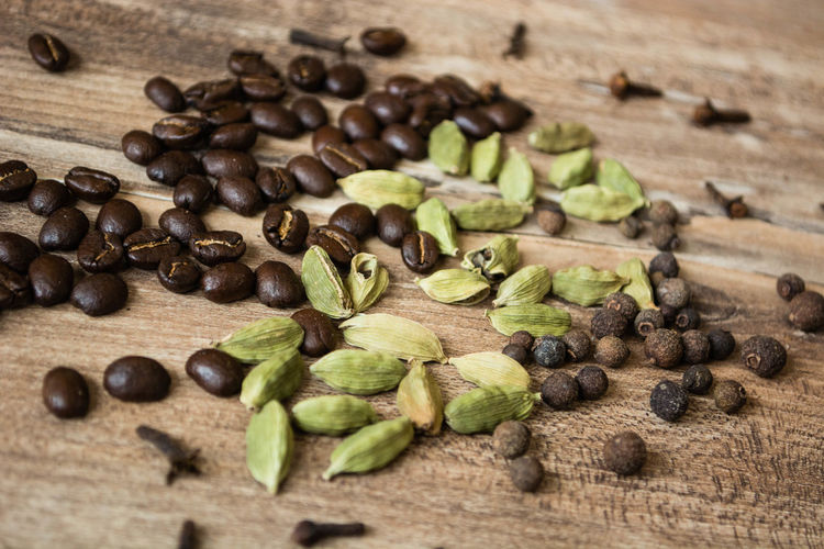 High angle view of roasted coffee beans by spices on wooden table