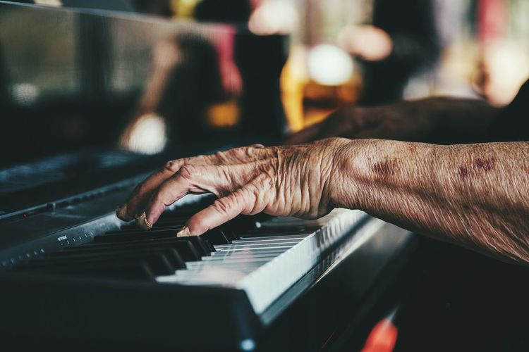 Cropped Hands Of Senior Person Playing Piano