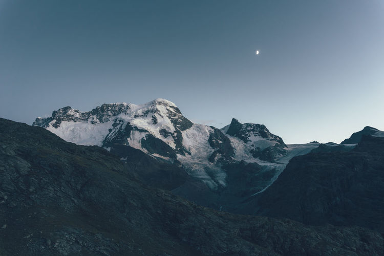 Scenic view of mountains against clear sky during sunset at swiss alps