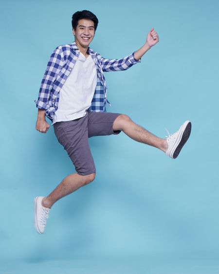 Portrait of young man jumping against blue background