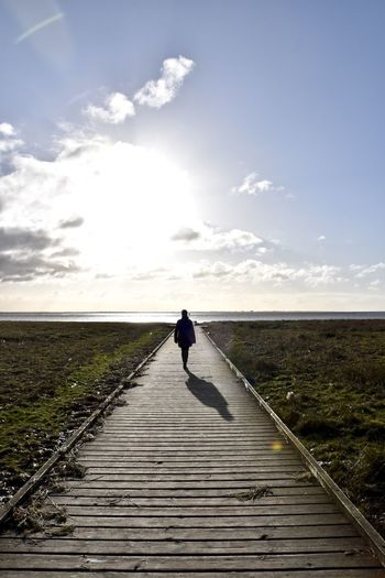 Rear view of woman walking on pier towards sea during sunny day