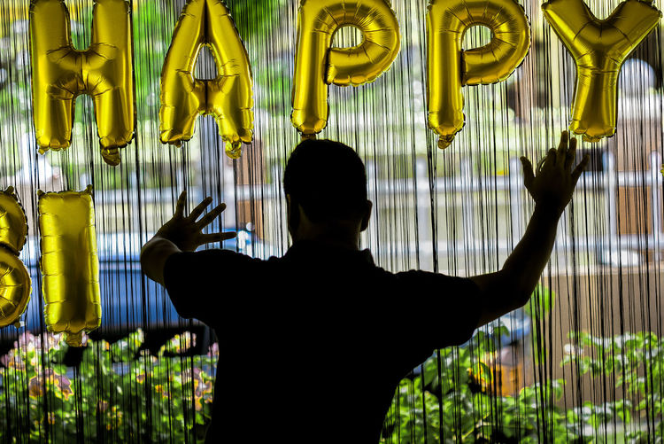 Rear View Of Man Doing Decoration During Birthday