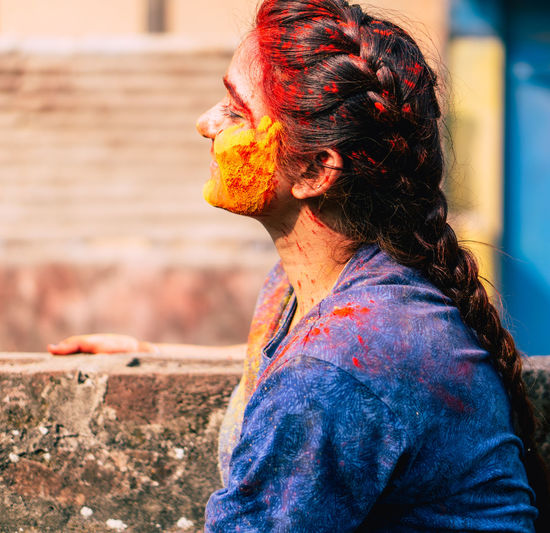 Side view of young woman with powder paint on face during holi