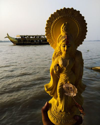 Statue of buddha sculpture against sea
