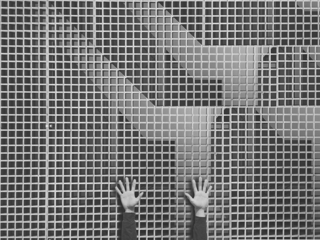 Hands against patterned wall