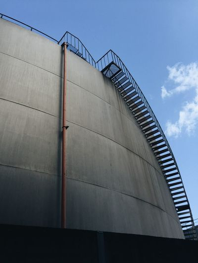Low angle view of staircase on silo against sky