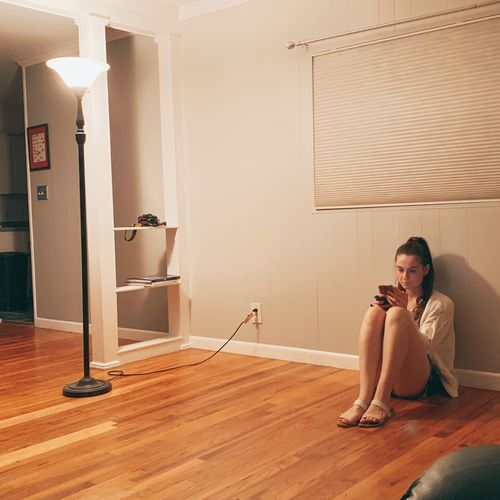 Woman sitting on wooden floor at home