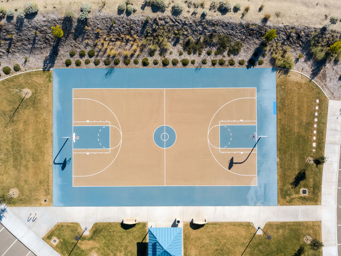 A basketball court from above Leisure Activity Day Sport Outdoors High Angle View Sunlight Shape Basketball Park Overhead View Top Down View Sports Court Blue Orange Color Grass Match - Sport Playground Competition Game No People