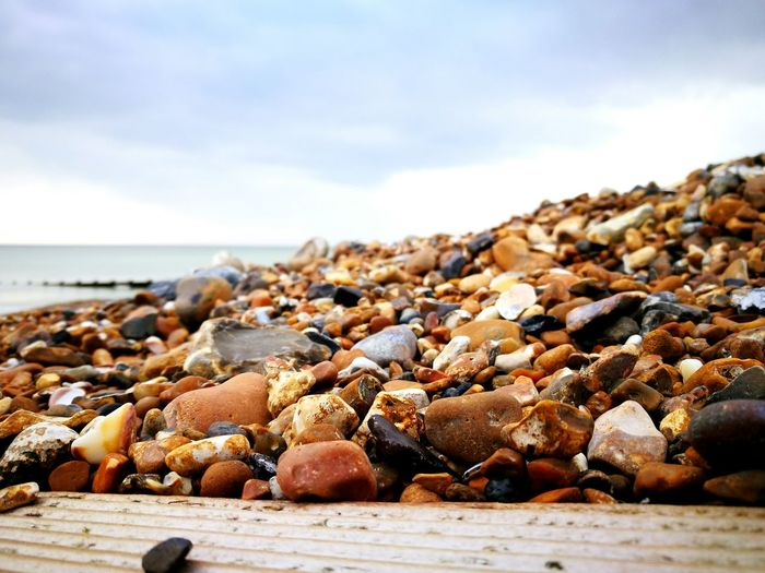Close-up of pebbles at beach against sky