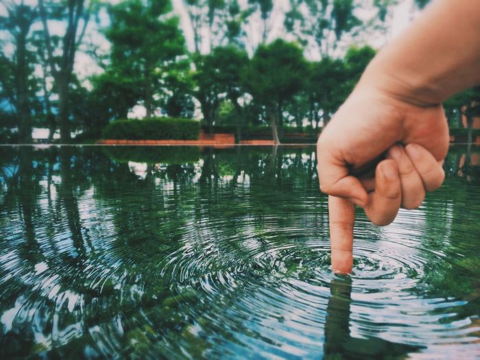 Tilt shift image of person touching water