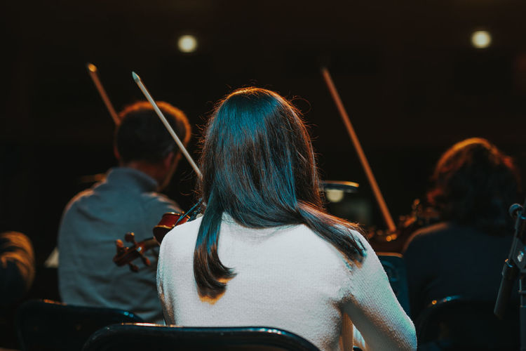 Rear view of woman playing violin during event