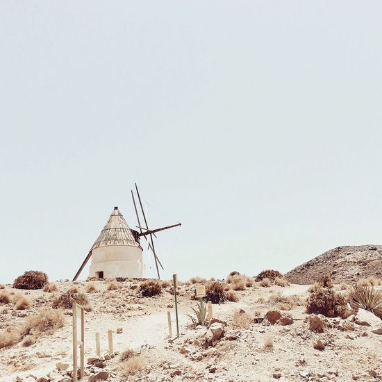 Traditional windmill on desert against clear sky