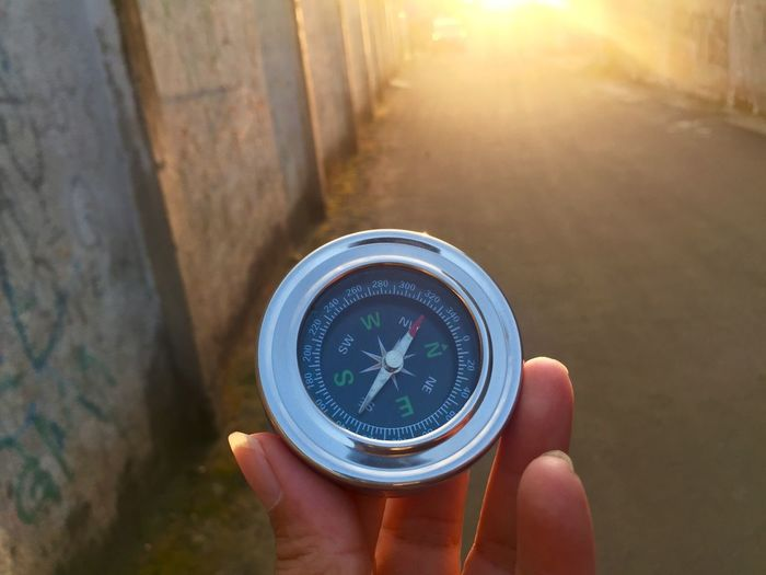 Compass Sunset Direction Human Hand Holding Navigational Compass Guidance Human Body Part Real People Navigational Equipment Hand Close-up Focus On Foreground Day One Person Accuracy Body Part Unrecognizable Person Exploration Sunlight High Angle View Outdoors