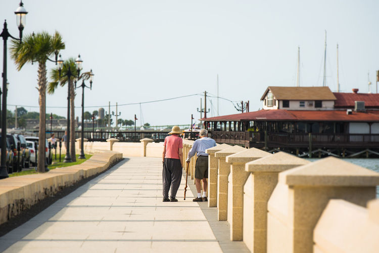 Rear View Of Senior Couple Walking On Pathway Against Sky During Sunny Day