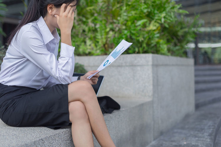 Businesswoman Holding Documents While Sitting On Retaining Wall In City