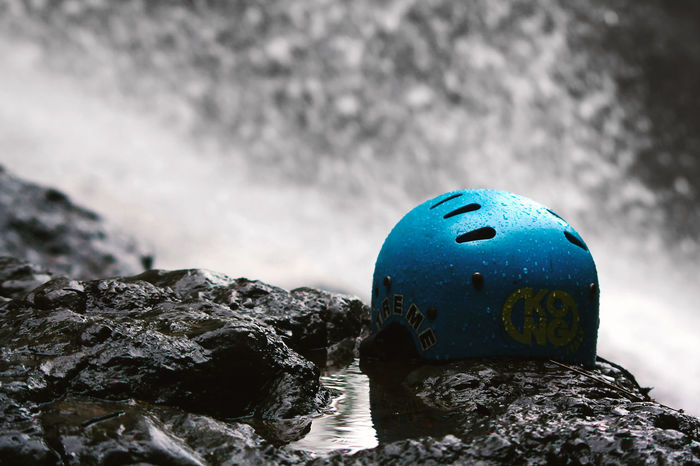 Blue helmets on the rock with water fall background Fall Beauty Rock Travel Photography Adventure Beauty In Nature Blue Close-up Day Helmets Nature No People Outdoors Product Photography Protection Rock - Object Sea Sky Textured  Water Waterfront