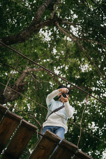 Low angle view of man photographing in forest