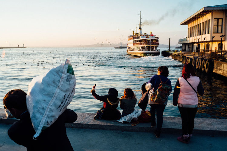Rear view of people walking on sea against sky