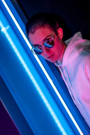 Portrait of woman wearing sunglasses against illuminated light