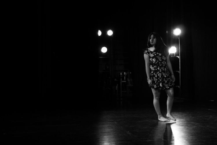 Full length of ballerina standing on stage in theater