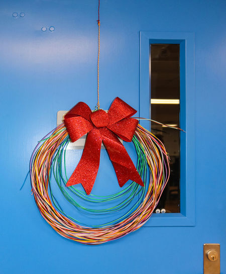 Network Cabling Christmas wreath with glittery bow hung on blue door with googly stick on eyeballs staring out Electronic High Tech Industrial Nerd Office Techies Cabling Celebration Christmas Data Digital Door Education Engineering Geeky Lab Network Season  Seasondoor Technology Telecommunication Telecommunications Equipment Unique Wire Wreath