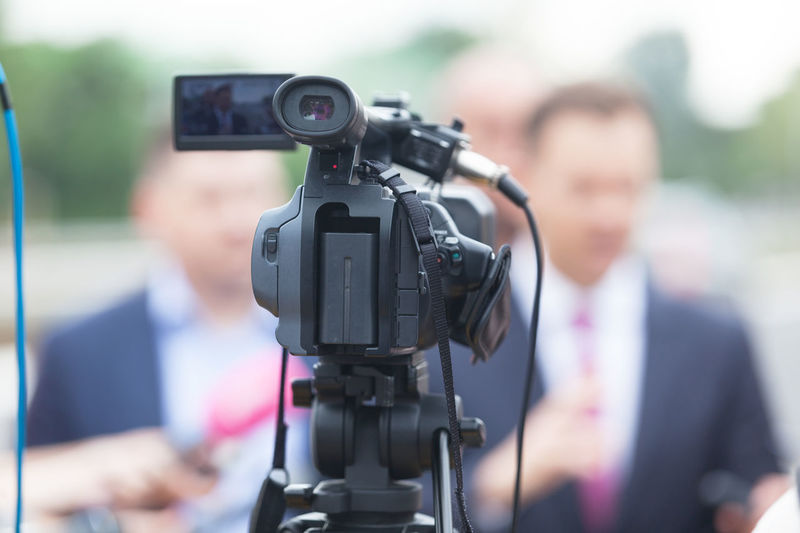 Close-Up Of Television Camera With Businessman In Background