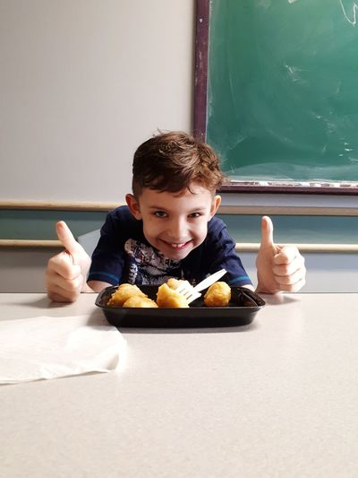 Portrait Of Happy Boy Showing Thumbs Up While Sitting With Food On Table In Classroom
