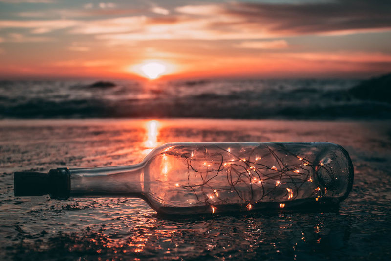 Close-up of string light in bottle at beach against sky during sunset