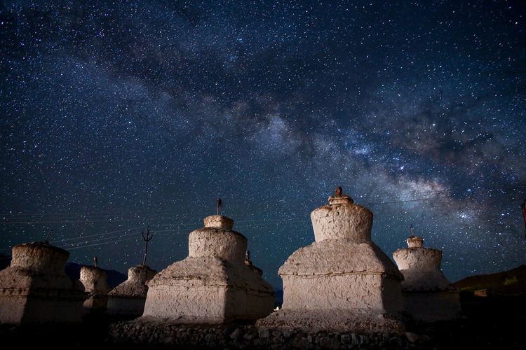 Low angle view of built structures against milky way at night
