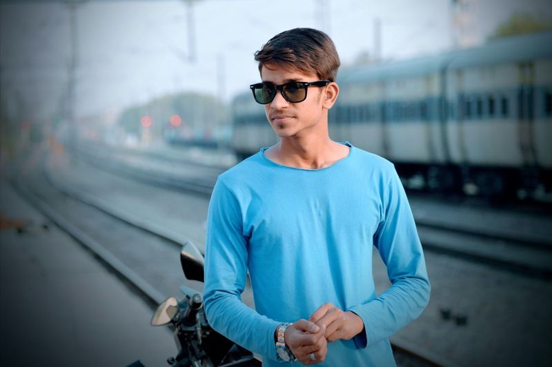 Young man wearing sunglasses with train in background