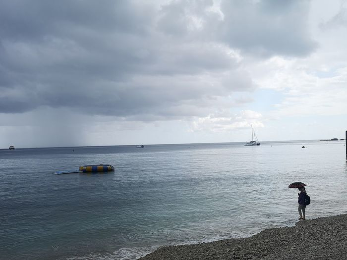 Woman with an umbrella standing on a beach, overlooking the ocean while the sky is cloudy Woman Clouds Cloud Rainy Grey Sky On Sea Ocean Lonely Sad Lonesome Water Nautical Vessel Photography Themes Sea Beach Low Tide Full Length Standing Silhouette Sky