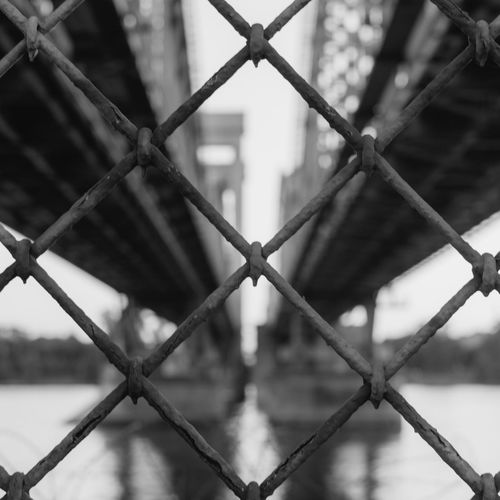 Full Frame Shot Of Chainlink Fence Against Bridge Over Sea