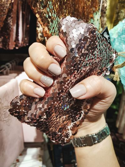Cropped hand of woman holding sequin purse at store