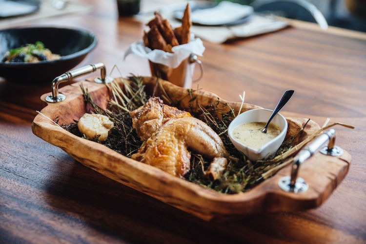 Roasted chicken with herbs, rosemary and garlic in wooden tray served with white sauce and peeled potato fries. Bowl Close-up Focus On Foreground Food Food And Drink Freshness Garnish Healthy Eating High Angle View Indoors  Kitchen Utensil No People Plate Ready-to-eat Seafood Selective Focus Serving Size Still Life Table Tray Wellbeing Wood - Material