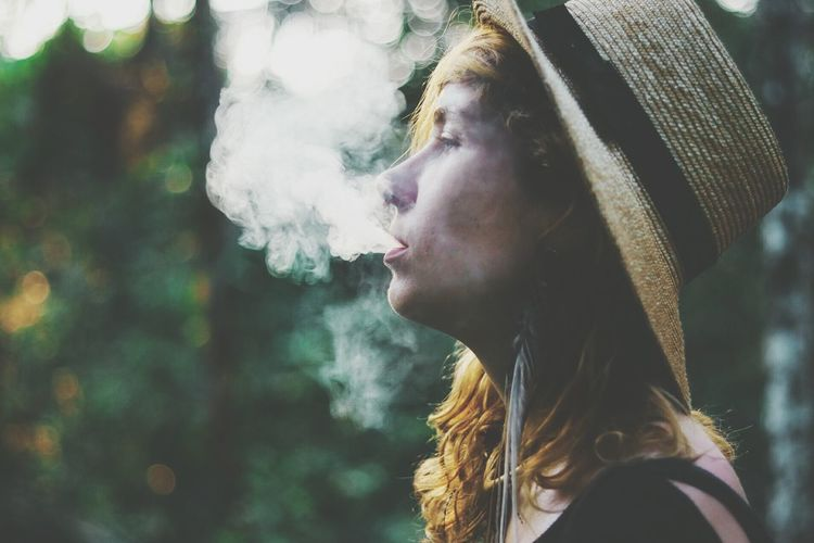 Close-up of woman exhaling smoke outdoors