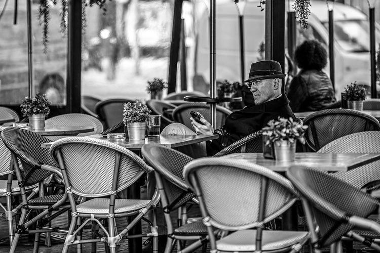 """Back to the '60s"" Black And White Black&white Blackandwhite Blackandwhite Photography Cafe City Coffee Day EyeEm Best Shots EyeEm Gallery EyeEmBestPics EyeEmNewHere Hat Men Outdoors People Real People Sitting The Portraitist - 2017 EyeEm Awards The Street Photographer - 2017 EyeEm Awards EyeEm Selects"