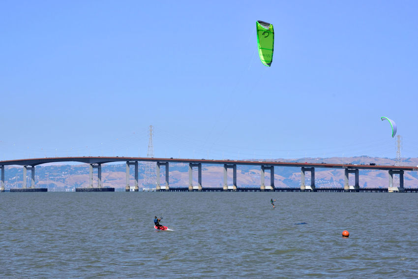Kiteboarding In San Mateo 17 San Mateo, Ca. The Color Of Sport Kitesurfers Kiteboarding San Mateo Bridge Power Towers Power Lines Bridge Span Traffic On Bridge Colorful Sails Watersports Aquactic Sports Wind Power Sports San Francisco Bay Eastbay Hills Kitesurfing Course Marker Calm WatersClear Blue Sky Enjoying Life Leisure Activity