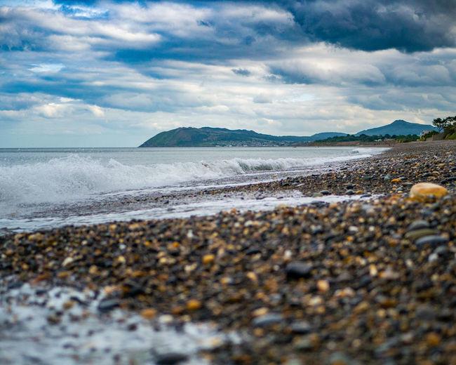 Surface level of beach against dramatic sky