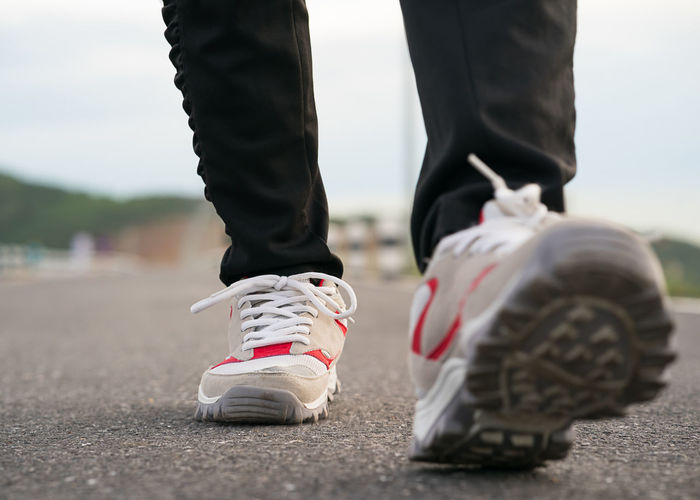 Low section of man in shoe walking on road