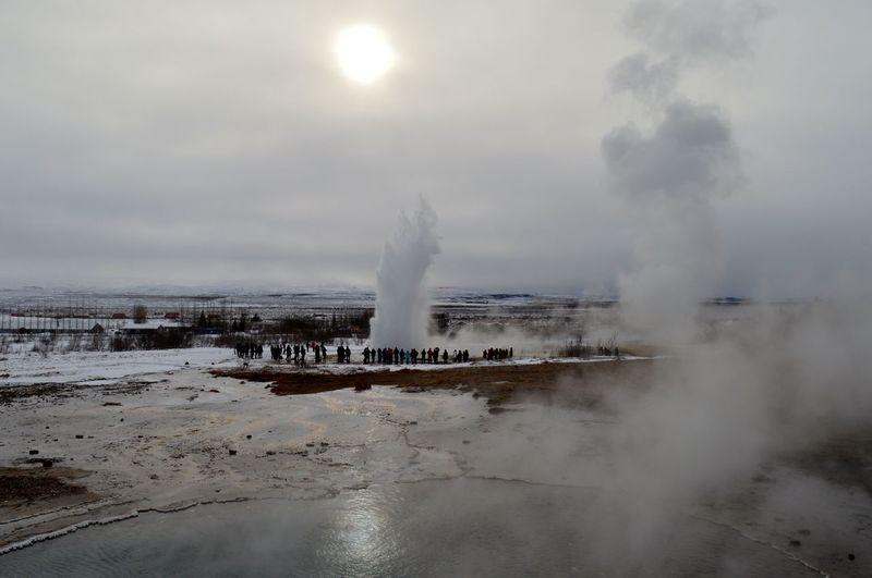 People at strokkur geyser erupting against sky