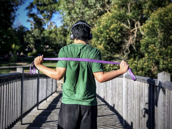 Rear view of man doing resistance band exercises while standing on footbridge.