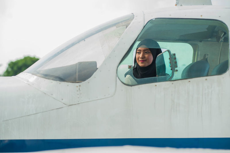 Young woman wearing hijab while sitting in airplane