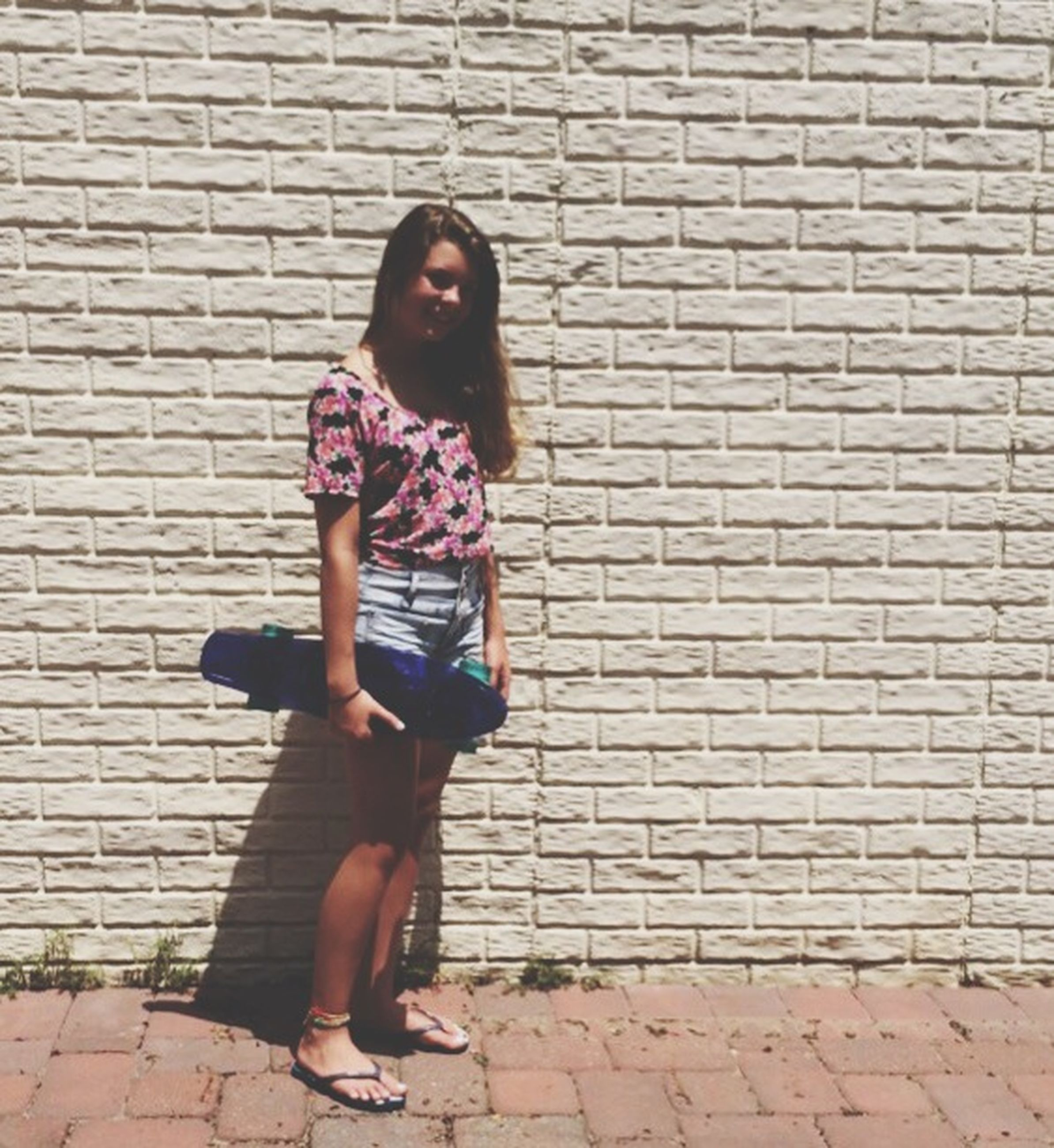 brick wall, lifestyles, cobblestone, full length, casual clothing, leisure activity, building exterior, wall - building feature, built structure, architecture, standing, stone wall, front view, sidewalk, young adult, outdoors, young women, day